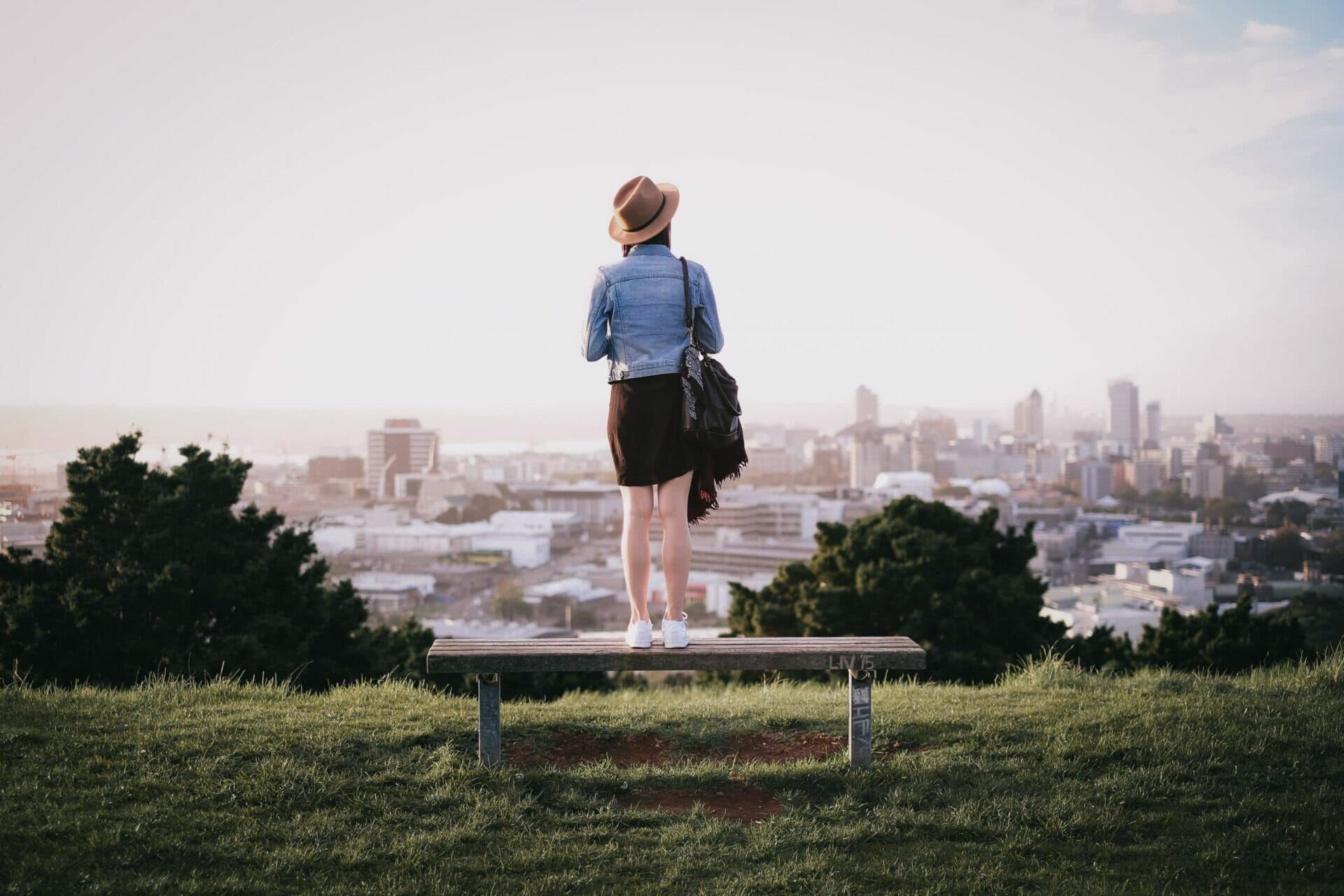 Girl standing on mountain top looking at city